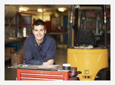 Apprentice leaning on a tool cabinet with a forklift behind him