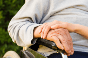Elderly person sitting down, focused on their crossed hands