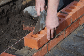 Bricklayer laying bricks in a line